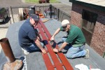Mike Starks of Eugene, Oregon and Dr. Doug Shearer of Toppenish attach the footboards for caboose 1238's catwalk to its roof.